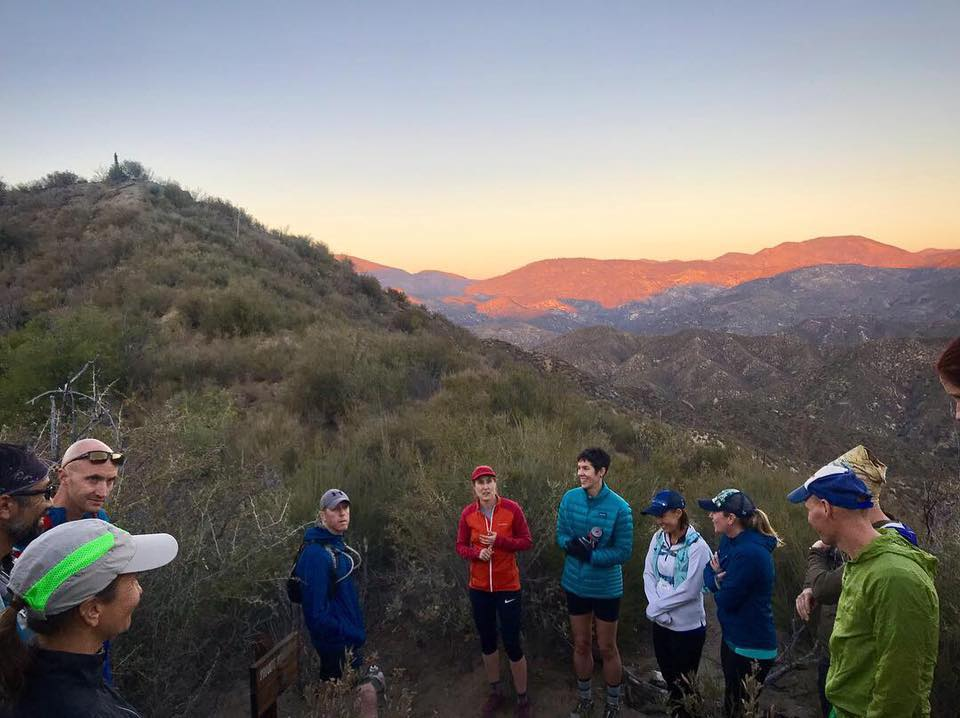 Cinda Brown (white jacket, blue hat) pauses with her group to watch a sunset over Southern California's San Gabriel Mountains at Band of Runners Trail Camp. PC: Dominic Grossman